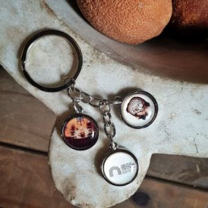 Museum key chain with three droplets containing the logo of the museum, a photo of the old operating theatre and a 19th century drawing of the head