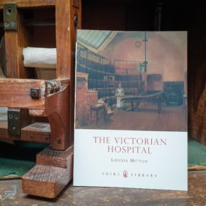 Cover of the book the Victorian Hospital next to a 19th century bandage dispenser
