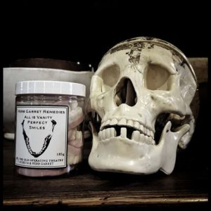 Still life with skull next to a pot of sweets that resemble dentures.