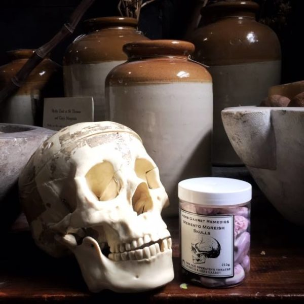 A still life in the herb garret containing ceramic pots in the background and a skull and a pot of sweets in the foreground.