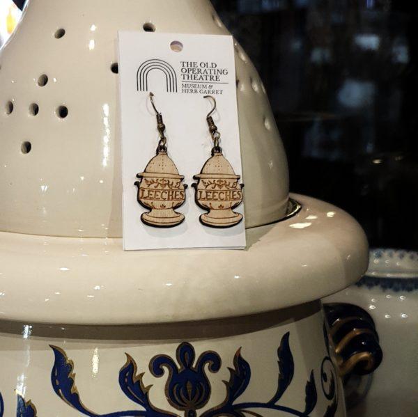 A pair of leech jar dangle earrings set against the original leech jar in the museum.