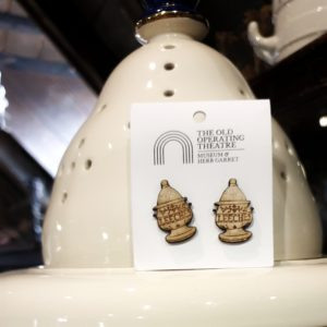 A pair of stud earrings in the shape of the museum's leech jar shown on picture.