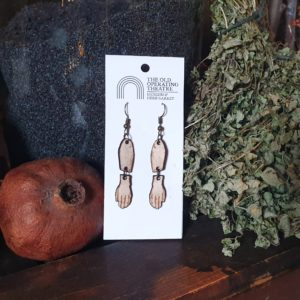 A pair of dangle earrings in the shape of an arm set against a still life or herbs and pomegrante.
