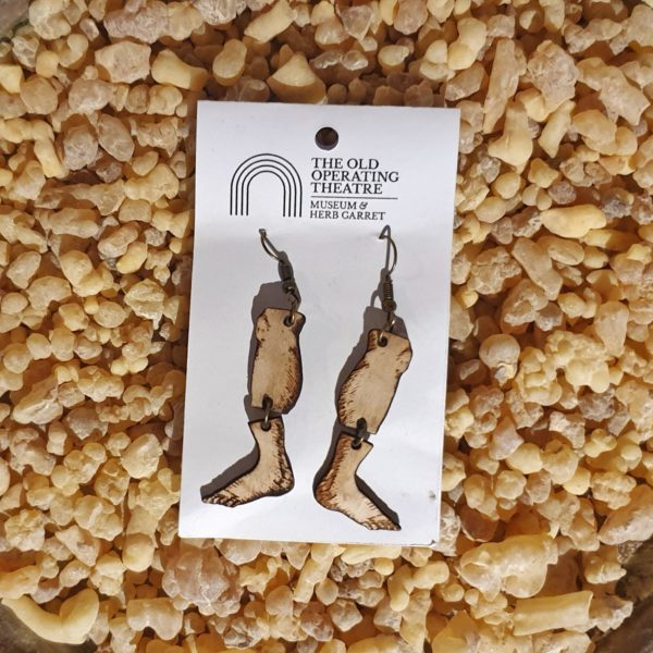 A pair of dangle earrings in the shape of legs.