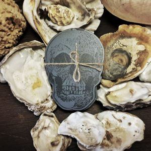 A set of 4 coasters in the shape of a skull next to oyster shells in the museum.