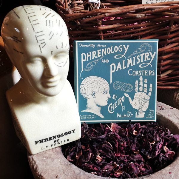 A box set of 6 coasters containing images of phrenology and palmistry set against a still life in the museum.