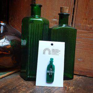 Green TR Digitialis Brooch set against green apothecary bottles.