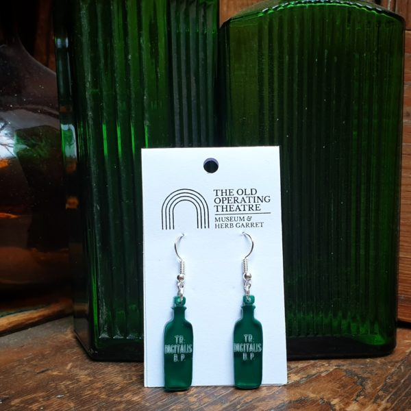 Green TR Digitalis Dangle Earrings set against other green apothecary bottles.