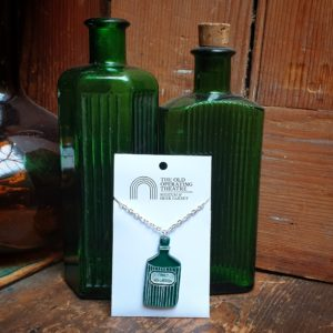 Green Belladonna Pendant set against two green apothecary bottles