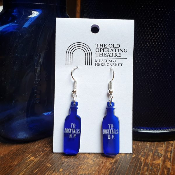 TR Digitalis dangle earrings set against two apothecary blue bottles.