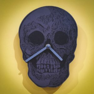 Still life of black and grey skull clock on yellow wall